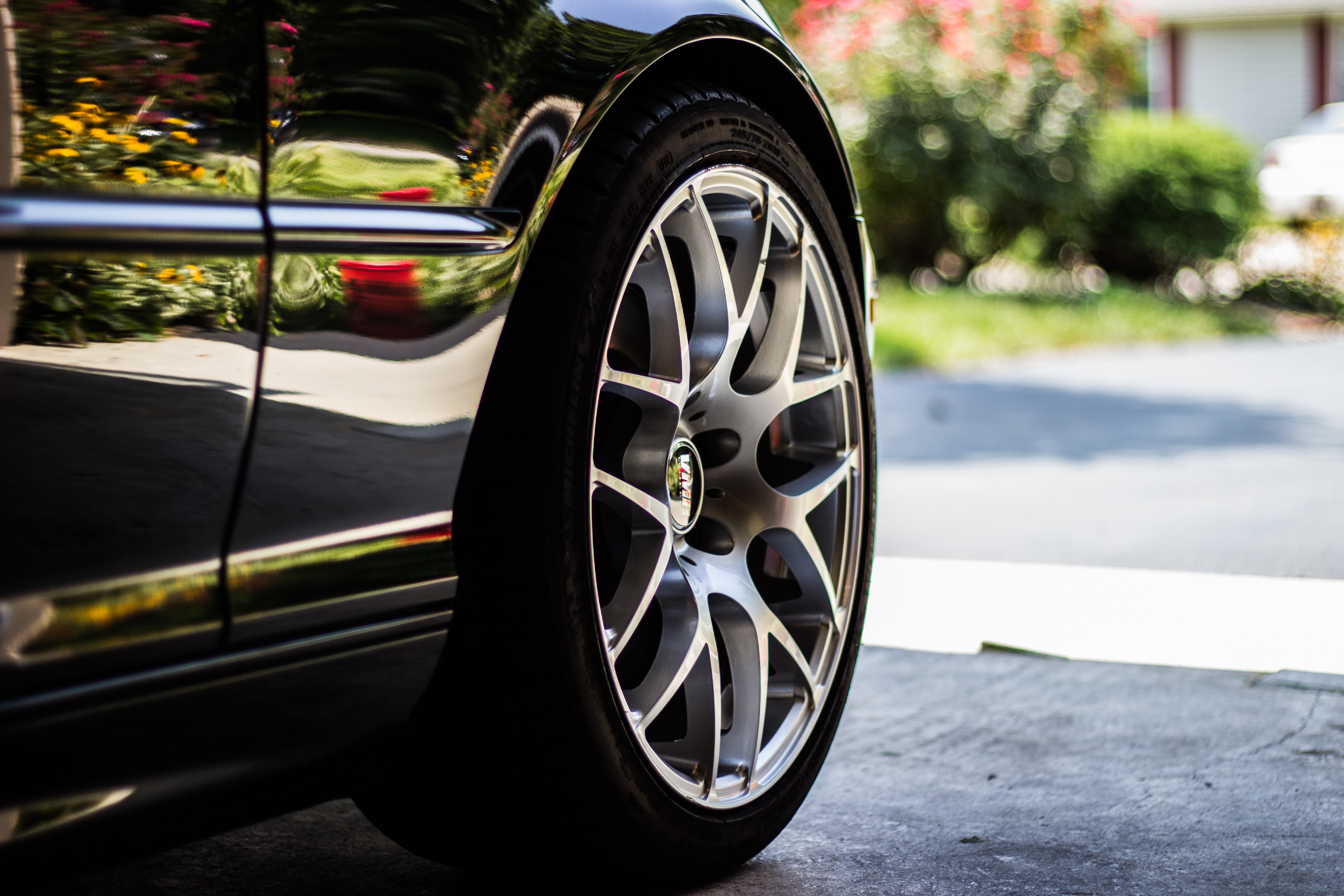 A car wheel and rim sitting on a concrete floor in a garage, the driveway visible beyond..