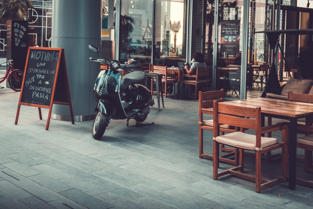 A scooter is parked outside on the patio of a restaurant.