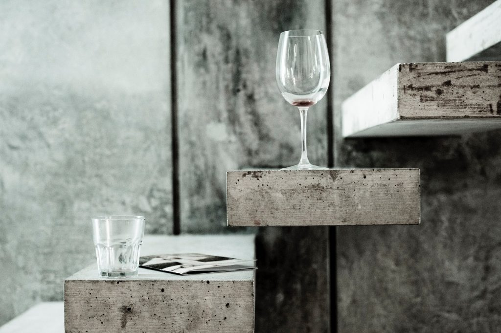 A wine and water glass placed on a set of concrete stairs inside a home