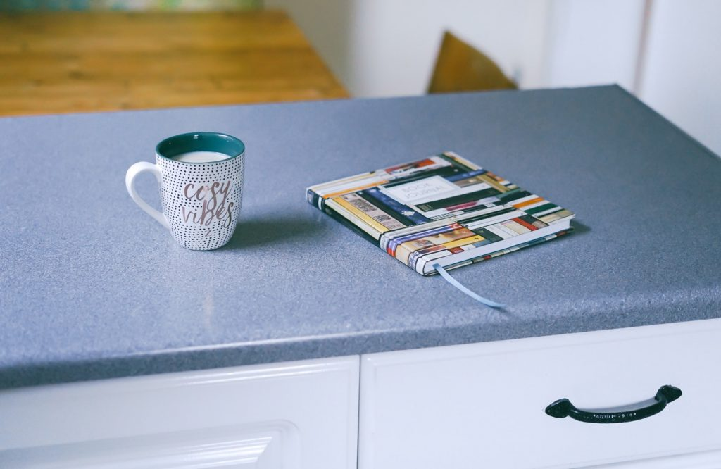 A mug and a book sit on top of a finished countertop.