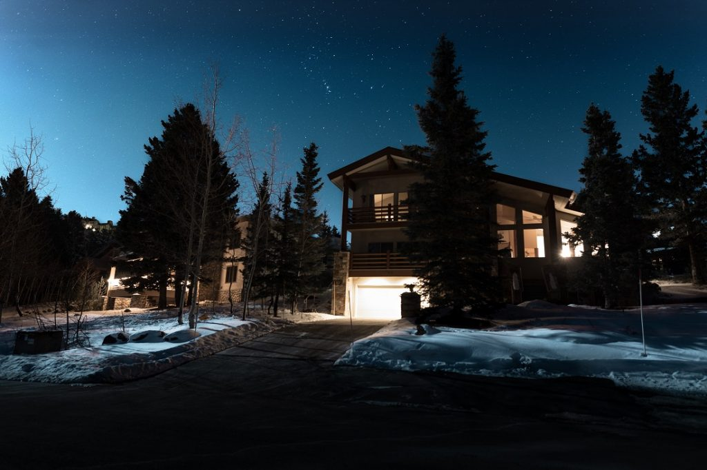 Home with a concrete driveway surrounded by snow pictured at night