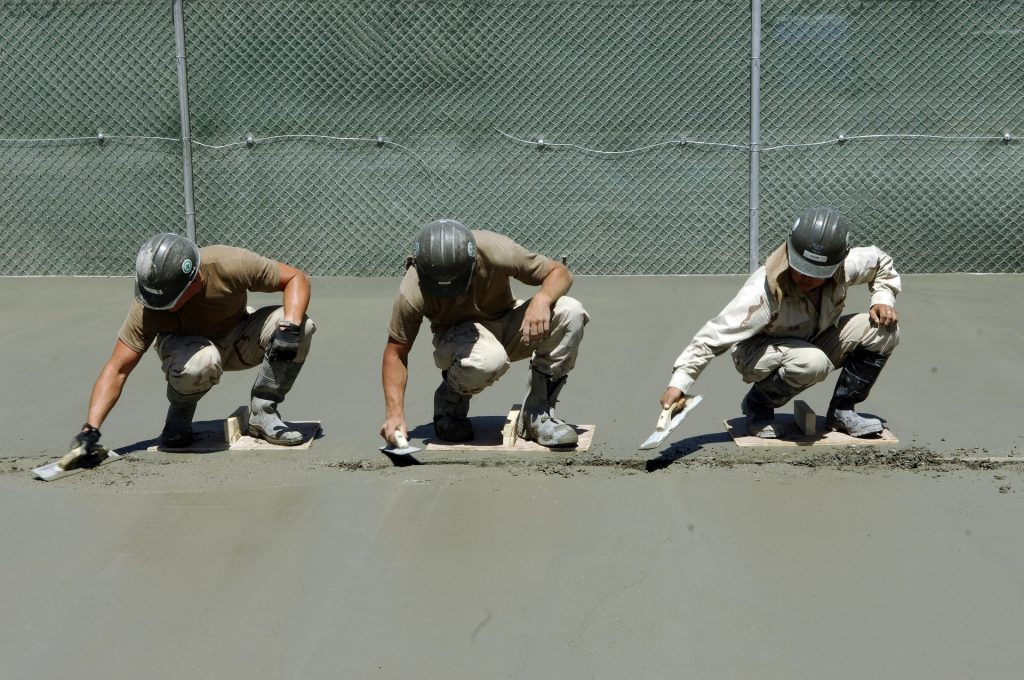 Three men lay concrete outside