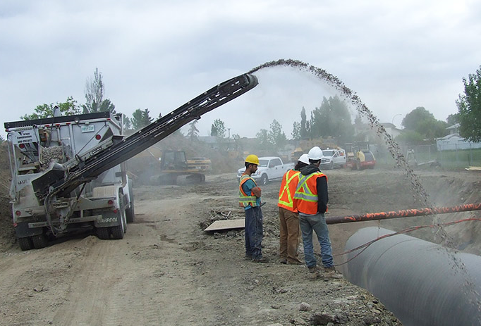 Construction workers using a stone slinger to transfer stone