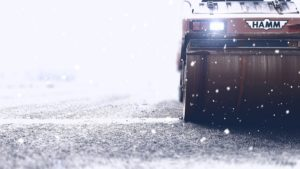 Road roller operates as snow falls