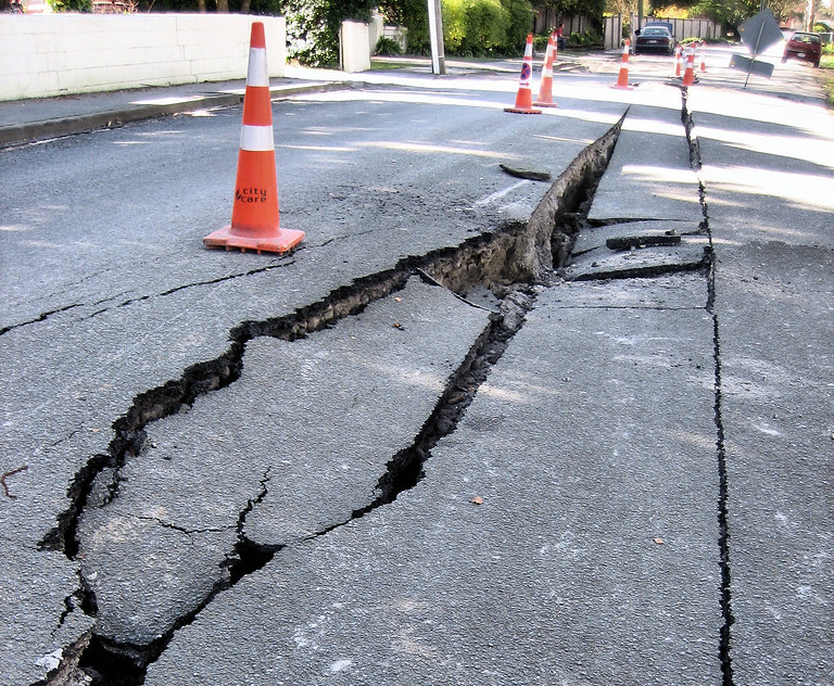 image of severely damaged and cracked road with pylons