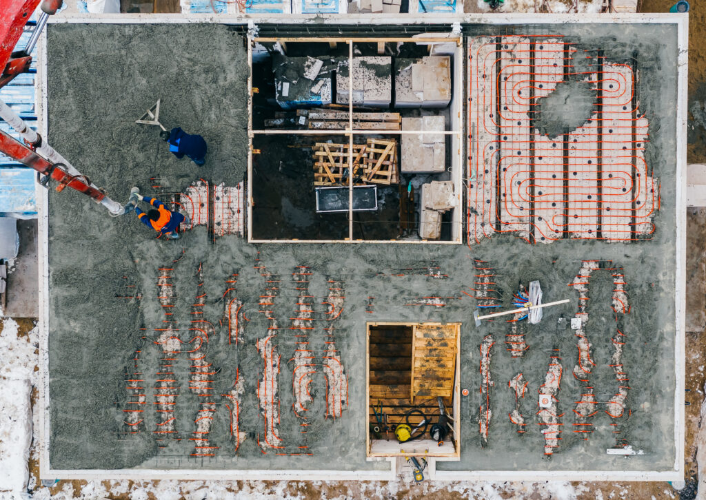 Aerial view of construction workers pouring a wet concrete at floor heating system installation in new house construction site